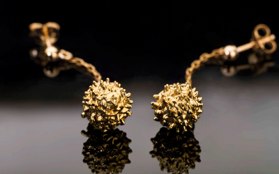 A pair of real pine-balls plated with 24K Gold.